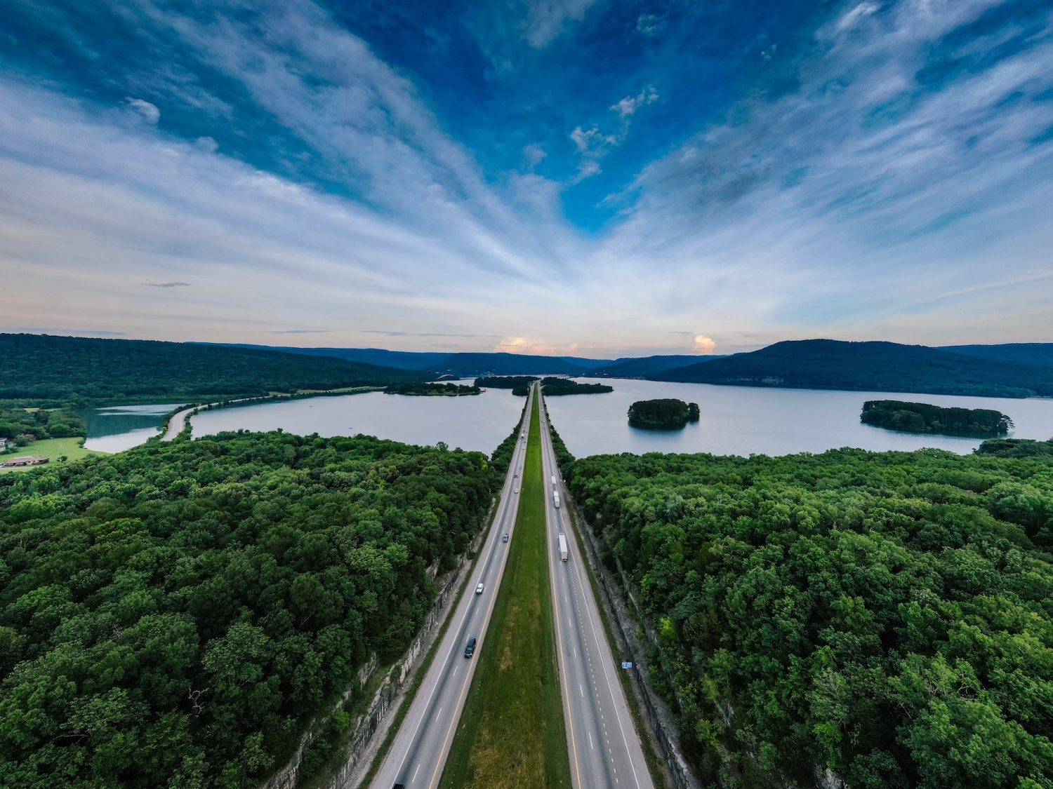 Drone shot above a scenic freeway and lake